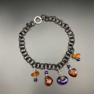 Collana girocollo da donna con anelli in corno nero, pendente a cuore in ambra e ametista G11620